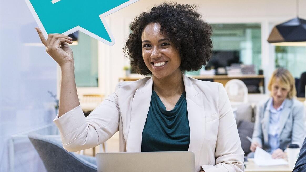 Frau im Büro hält eine Social Media Bubble hoch und lächelt / Artikel Corporate Influencer